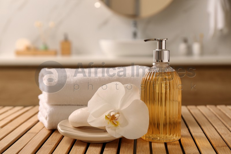 Composition with liquid soap in glass dispenser on wooden table indoors