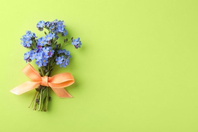 Beautiful blue forget-me-not flowers tied with ribbon on light green background, top view. Space for text