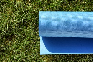 Bright exercise mat on fresh green grass outdoors, top view