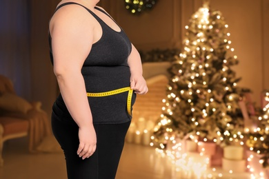 Overweight woman measuring her waist in room with Christmas tree after holidays, closeup