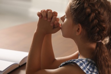 Cute little girl praying over Bible at table indoors, closeup