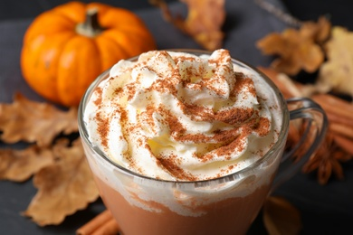 Delicious pumpkin latte with whipped cream on table, closeup