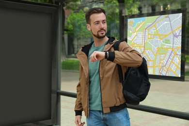 Young man with backpack waiting for public transport at bus stop