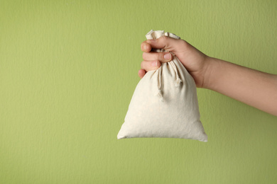 Woman holding full cotton eco bag on light green background, closeup