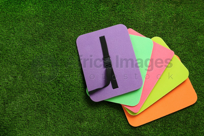 Bright foam tourist seat mats on green grass, flat lay. Space for text