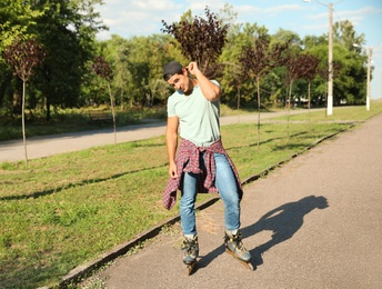 Handsome young man roller skating in park, space for text
