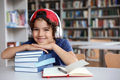 Cute little boy with headphones and books at table in library reading room