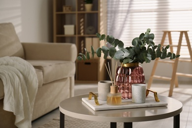 Bunch of eucalyptus branches and oil diffuser on table in living room. Interior design