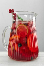 Glass jug of Red Sangria on white wooden table, closeup