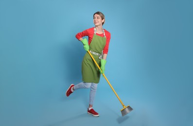 Young housewife with broom on light blue background