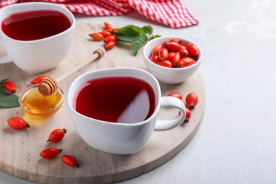 Fresh rose hip tea and berries on light table