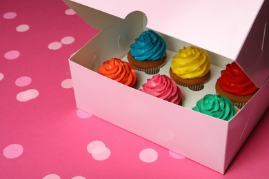 Box with different cupcakes and confetti on pink background