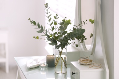 Beautiful eucalyptus branches on dressing table in room. Interior design