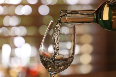 Pouring white wine from bottle into glass on blurred background, closeup