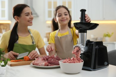 Happy family making dinner together in kitchen, daughter using modern meat grinder while mother cutting carrot
