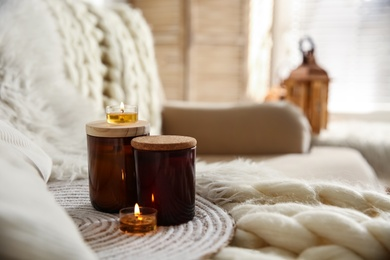 Candles on beige sofa with knitted blanket. Interior design