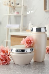 Hair care cosmetic products and beautiful flowers on light grey table in bathroom