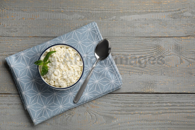 Delicious fresh cottage cheese with basil on grey wooden table, flat lay. Space for text