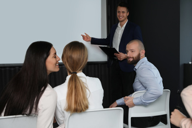 Business people at seminar in conference room with video projection screen