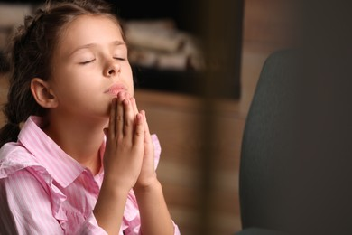 Cute little girl with hands clasped together praying at home. Space for text