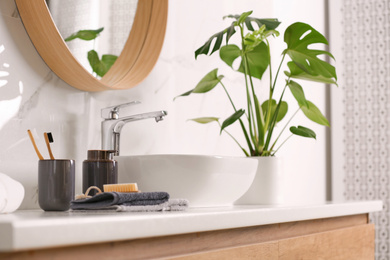Toiletries and stylish vessel sink on light countertop in modern bathroom