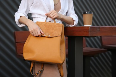 Young woman with stylish backpack in outdoor cafe, closeup