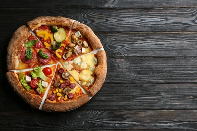 Slices of different delicious pizzas on black wooden table, top view. Space for text
