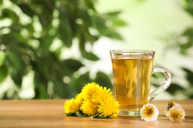 Delicious fresh tea, dandelion flowers and ice cubes on wooden table against blurred background. Space for text