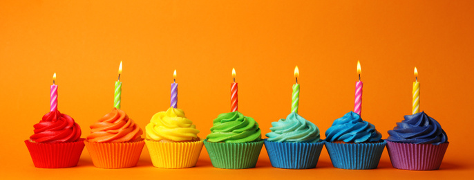 Delicious birthday cupcakes with burning candles on orange background