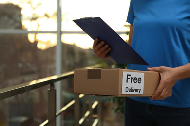 """Courier holding parcel with sticker """"Free Delivery""""  and clipboard indoors, closeup"""
