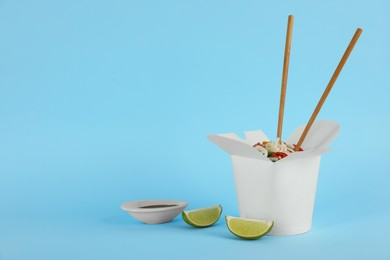 Box of vegetarian wok noodles with chopsticks, lime and soy sauce on light blue background. Space for text