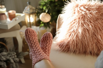 Woman wearing pink knitted socks in room decorated  for Christmas, closeup