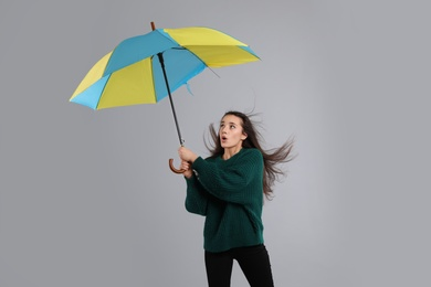 Emotional woman with umbrella caught in gust of wind on grey background