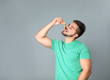Handsome man eating pizza on grey background, space for text