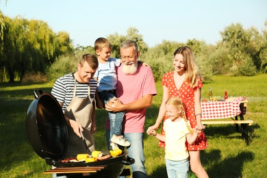 Happy family having barbecue in park on sunny day