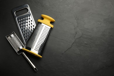 Different modern graters on black table, flat lay. Space for text