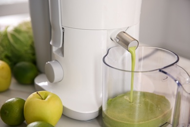 Modern juicer and fresh fruits on table in kitchen, closeup
