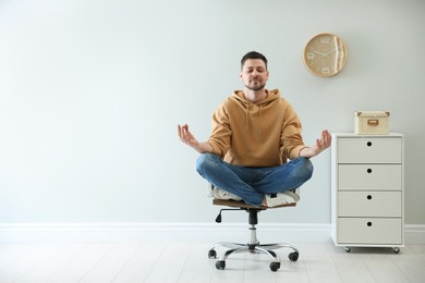 Calm man meditating in office chair at work. Space for text