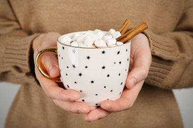 Woman holding cup of delicious hot chocolate with marshmallows and cinnamon sticks, closeup