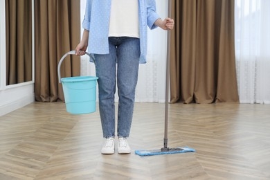 Woman with mop and bucket indoors, closeup. Cleaning service