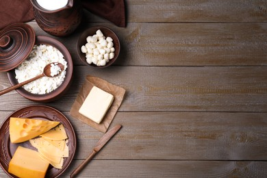 Flat lay composition with dairy products and clay dishware on grey wooden table. Space for text