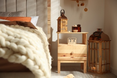 Vintage lantern and candles on wooden nightstand in bedroom. Interior design