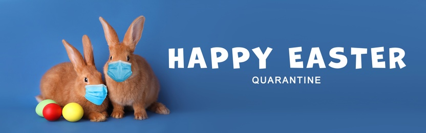 Text Happy Easter Quarantine and cute bunnies in protective masks on blue background, banner design. Holiday during Covid-19 pandemic
