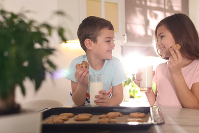 Cute little children eating cookies with milk in kitchen. Cooking pastry