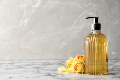 Stylish dispenser with liquid soap and beautiful flowers on white marble table, space for text