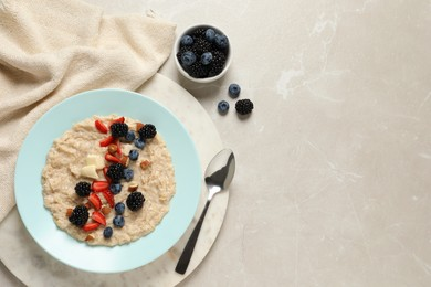 Tasty oatmeal porridge with berries and almond nuts served on light table, flat lay. Space for text