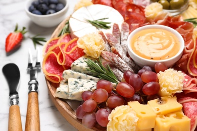 Wooden plate with different delicious snacks on white marble table, closeup