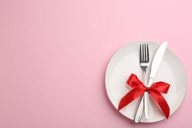 Beautiful table setting on pink background, top view with space for text. Valentine's Day dinner