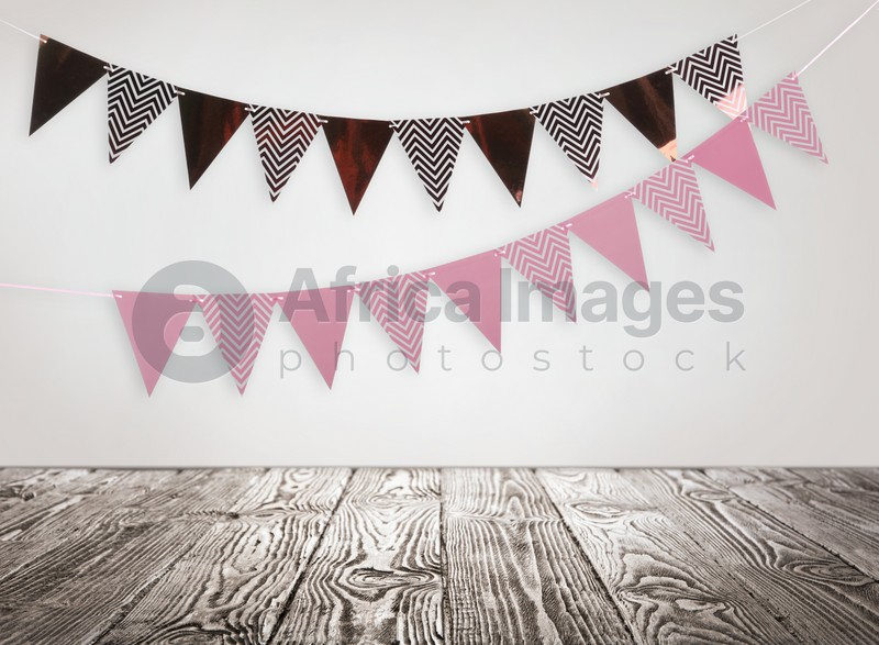 Empty wooden table and decorative bunting flags hanging on white wall