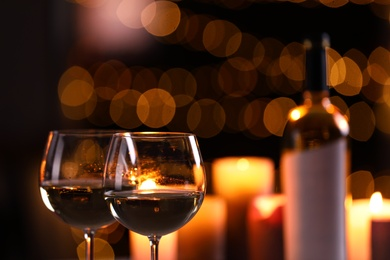 Glasses of wine and blurred view of burning candles on background